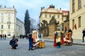 PRAGUE, CZECH REPUBLIC - JANUARY 22, 2019: Unidentified woman and boy observe staging (warrior with sword) at gates of Prague Castle