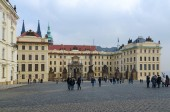 Tourists on Hradchanskaya square. Gate of Titans and Gate of Mathias, Prague Castle