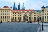 Tourists walk along Hradchanskaya Square. Gate of Titans and Gate of Mathias, Prague Castle