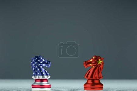 Échecs de chevalier du drapeau américain et les échecs de chevalier du drapeau chinois s'affrontent sur un plateau transparent. Chess Knight tête à tête. Confrontation et concept de guerre commerciale.