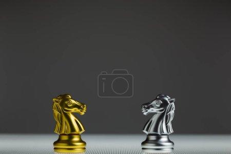 Les échecs de chevalier d'or et les échecs de chevalier d'argent s'affrontent sur un plateau transparent. Chess Knight tête à tête. Concept de confrontation.