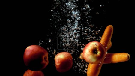 Photo for Fresh fruits apples and carrots falling in water with air bubbles - Royalty Free Image
