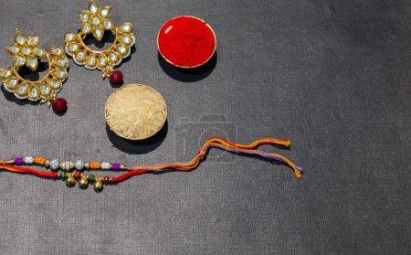 Photo pour Festival indien, fond Raksha Bandhan avec un élégant Rakhi coloré, Cadeau, Grains de riz et Kumkum. Un bracelet traditionnel indien qui symbolise l'amour entre frères et sœurs. - image libre de droit