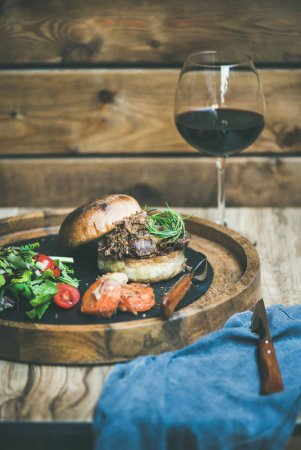 Pulled pork meat burger with vegetables and glass of red wine