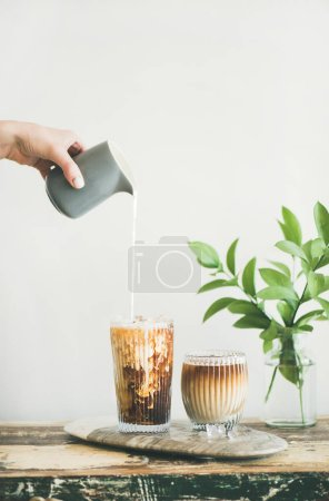 Iced coffee in tall glasses with milk poured over from pitcher by hand, white wall and green plant branches in vase at background