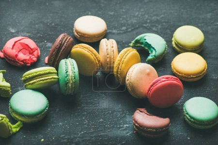 Sweet colorful French macaroon cookies dessert variety over black background