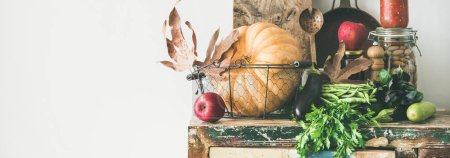 Photo for Autumn seasonal food ingredients, kitchen utensils. Vegetables, pumpkin, apples, canned food, fallen leaves over rustic chest of cupboard - Royalty Free Image