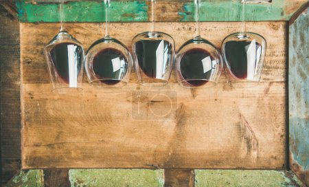 Photo for Red wine in glasses in row over rustic wooden tray background - Royalty Free Image
