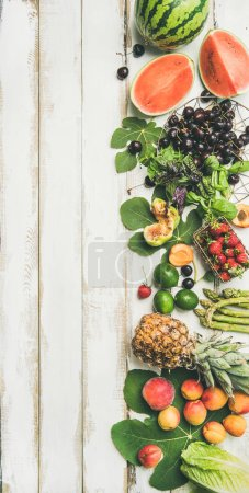 Photo for Seasonal fruit, vegetables and greens over white wooden background - Royalty Free Image