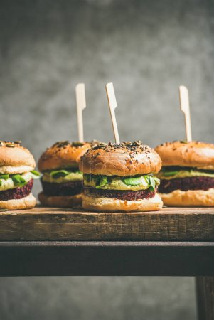 Photo for Healthy vegan burgers with quinoa beetroot patties, avocado cream and green sprouts on wooden board, grey wall at background - Royalty Free Image