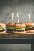 """Постер, картина, фотообои """"Здоровые веганский гамбургеры с киноа свекла пирожки, авокадо крем и зеленые ростки на деревянную доску, серые стены на фоне"""""""