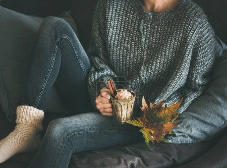 Woman in woolen sweater and jeans sitting and holding mug with hot chocolate or coffee with whipped cream and cinnamon and fallen leaf