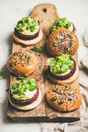 Photo for Healthy vegan burgers with quinoa beetroot patties, avocado cream and green sprouts on wooden board over light background, selective focus . Vegetarian, clean eating food - Royalty Free Image