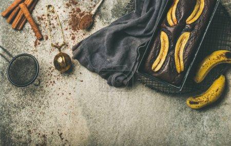 Flache Lage aus frisch gebackenem Bitterschokolade-Bananenbrot-Dessert in Backform auf Kühlgestell mit Zimt und Kakaopulver über grauem Betontischhintergrund, Draufsicht, Kopierraum