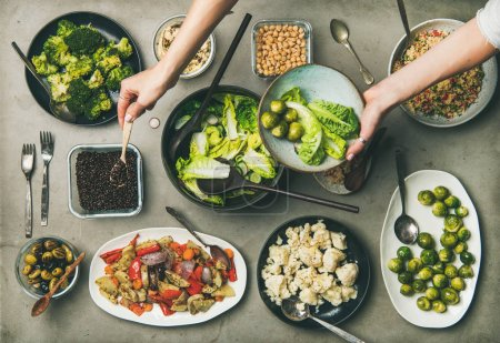 Photo for Vegan dinner table setting. Healthy dishes in plates on table. Flat-lay of vegetable salads, legumes, beans, olives, sprouts, hummus and woman hands mixing ingredients on plate, top view - Royalty Free Image