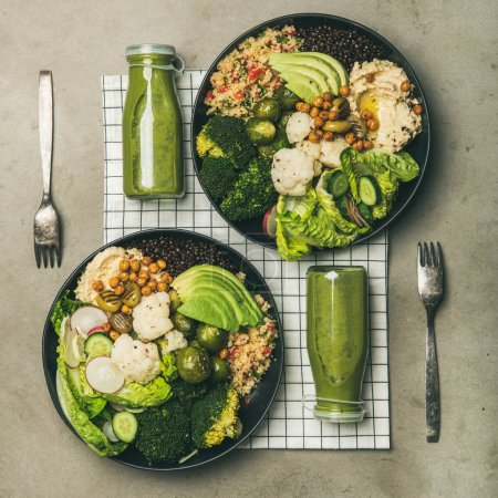 Photo for Healthy dinner, lunch setting. Flat-lay of vegan superbowls or Buddha bowls with hummus, vegetables, fresh salad, beans, couscous and avocado and green smoothies in bootles, top view, square crop - Royalty Free Image