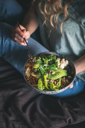 Photo for Healthy dinner or lunch. Curly woman in t-shirt and jeans sitting and eating vegan superbowl or Buddha bowl with hummus, vegetable, fresh salad, beans, couscous and avocado. Clean eating food concept - Royalty Free Image