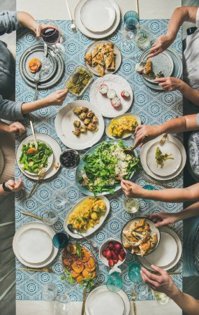 Mediterranean style dinner. Flat-lay of table with salad, starters, pastries over blue table cloth with hands holding drinks, sharing food, top view. Holiday vegetarian party concept