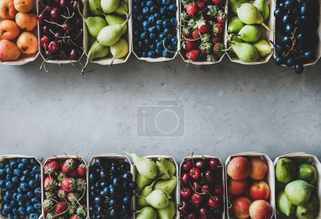 Photo for Summer fruit and berry variety. Flat-lay of ripe strawberries, cherries, grapes, blueberries, pears, apricots, figs in wooden eco-friendly boxes over grey background, top view, copy space - Royalty Free Image