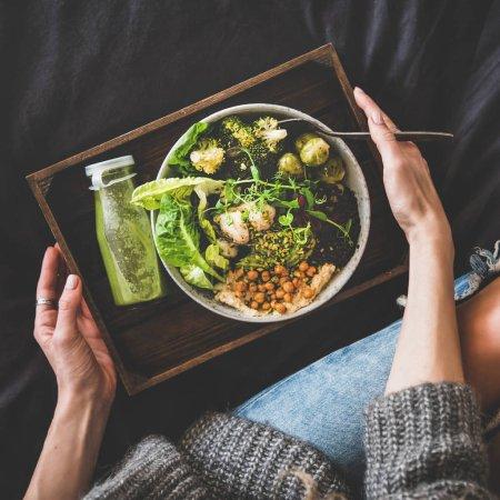 Photo pour Dîner sain, déjeuner au lit. Superbol végétalien ou bol Bouddha avec houmous, légumes, salade fraîche, haricots, couscous et avocat, smoothie vert sur plateau et femme en jeans manger, vue sur le dessus, culture carrée - image libre de droit