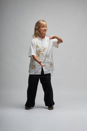 Photo for Mature blonde woman practicing Chi kung and Tai Chi on a white background. She wears a traditional white chinese Tai Chi jacket, black trousers and black shoes with ying yang symbol - Royalty Free Image