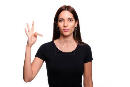 Photo pour Isolé en fond blanc femme brune disant lettre T en langue des signes espagnole - image libre de droit