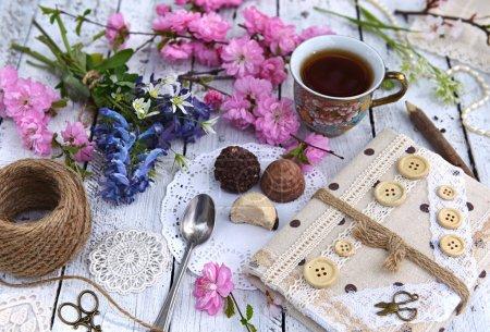 Photo pour Fleurs sauvages, branches de cerisier en fleurs, tasse de thé et journal sur planches. Printemps nature morte, beau fond rural avec des fleurs de saison dans un style vintage . - image libre de droit