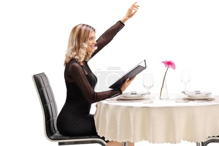 Young woman seated at a restaurant table calling the waiter isolated on white background