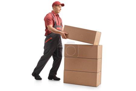 Photo pour Coup de profil de toute la longueur d'un mover plaçant un paquet sur le dessus une pile isolé sur fond blanc - image libre de droit