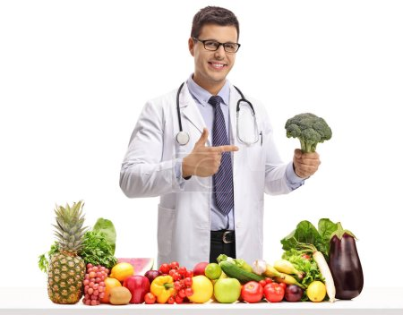 Doctor with broccoli pointing behind a table with fruit and vegetables isolated on white background