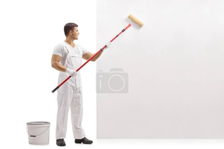 Full length profile shot of a painter painting a wall with a paint roller isolated on white background