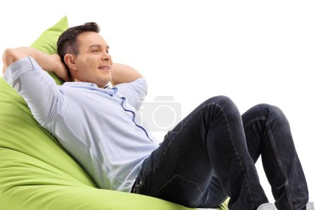 Photo for Relaxed young man sitting on a beanbag isolated on white background - Royalty Free Image