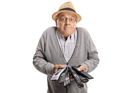 Confused elderly man with remotes isolated on white background