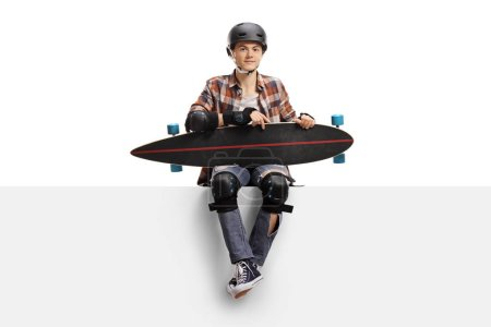 Photo for Teenage skater with protective equipment and a longboard sitting on a panel isolated on white background - Royalty Free Image