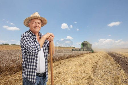 Elderly farmer on a wheat field with a combine harvester