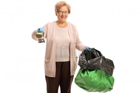 Elderly woman holding a tin can and a garbage bag isolated on white background
