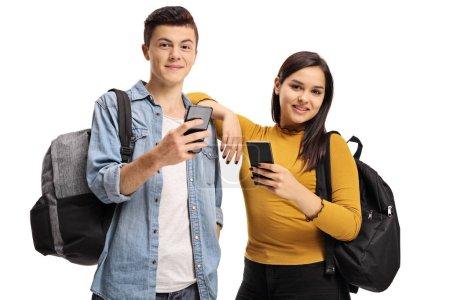 Photo pour Adolescent garçon et fille souriant et tenant des téléphones cellulaires isolés sur fond blanc - image libre de droit
