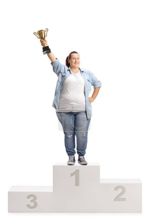 Overweight woman holding a gold trophy cup and standing on a winner's pedestal isolated on white background