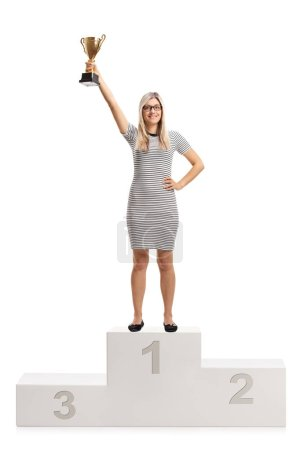Full length portrait of a young woman on a winner's pedestal holding a gold trophy cup isolated on white background