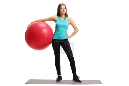 Full length portrait of a young female with a pilates ball standing on an exercise mat isolated on white background
