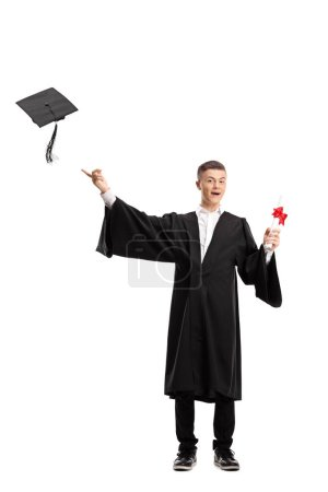 Photo for Full length portrait of a graduate student holding a diploma and throwing a graduation hat isolated on white background - Royalty Free Image