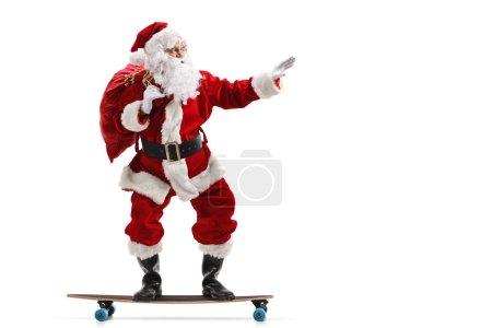 Photo pour Photo de profil pleine longueur du Père Noël chevauchant un longboard isolé sur fond blanc - image libre de droit