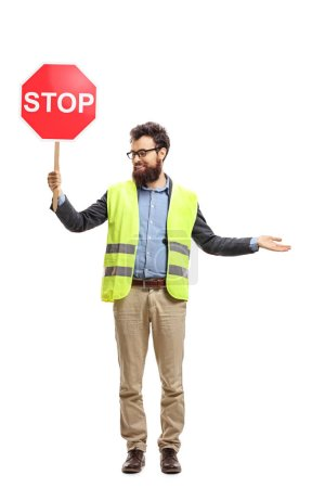 Photo for Full length portrait of a man with a safety vest holding stop sign gesturing with hand and looking to one side isolated on white background - Royalty Free Image