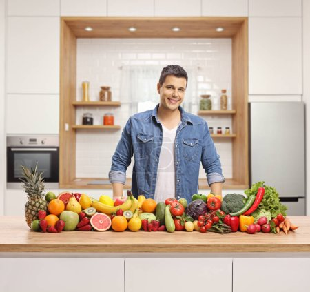 Photo for Young handsome man with a variety of fruits and vegetables on a wooden counter in a kitchen - Royalty Free Image