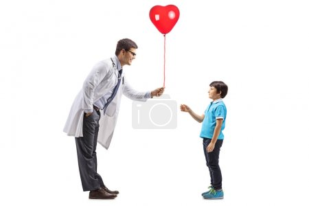 Photo pour Full length profile shot of a male doctor giving a red heart balloon to a little boy isolated on white background - image libre de droit