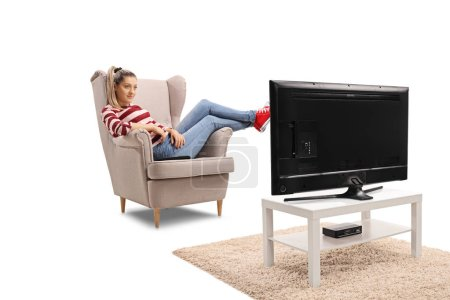 Photo for Young woman watching television and sitting in an armchair isolated on white background - Royalty Free Image