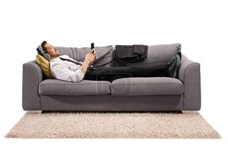 Photo pour Plan complet d'un homme d'affaires allongé sur un canapé et écoutant de la musique isolée sur fond blanc - image libre de droit