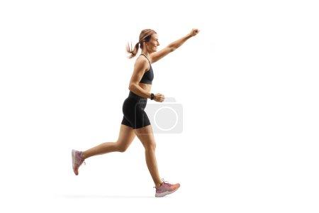 Photo pour Plan de profil pleine longueur d'une jeune femme en forme courant avec le bras levé isolé sur fond blanc - image libre de droit