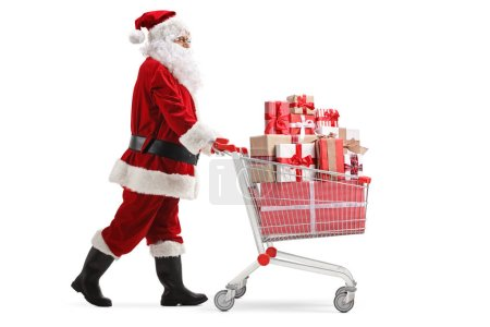 Photo for Full length profile shot of Santa Claus pushing a cart full of presents isolated on white background - Royalty Free Image