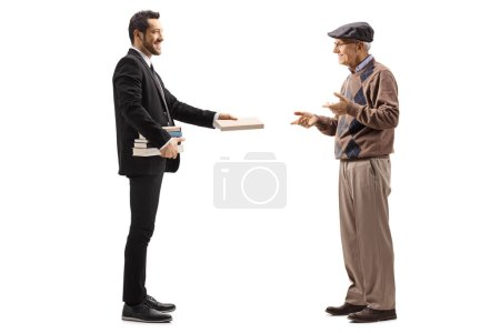 Photo for Full length profile shot of a young man in a black suit giving a book to an elderly man isolated on white background - Royalty Free Image